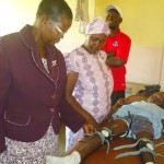 A young girl is having her leg braces fitted to her legs. The SOCKS representative, Riphath Onyongo, in the red shirt, and his wife Pauline, in the purple jacket, were instrumental in purchasing this equipment for the students